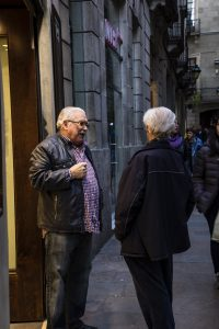 Two residents talk in front of a store in Barcelona, Spain