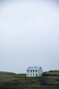 A single white house sands atop a hill in Iceland