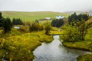 Guesthouses overlook a meandering river in Iceland